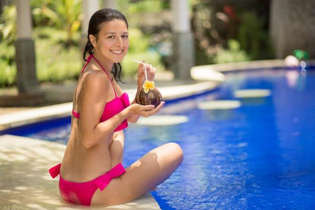 Девушка в розовом купальнике отдыхает на краю бассейна с напитком из кокоса.