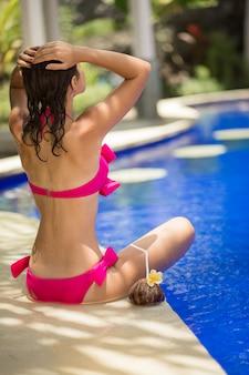 Девушка в розовом купальнике отдыхает на краю бассейна с напитком из кокоса