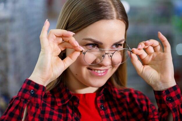 셔츠를 입은 소녀는 안경을 벗고 측정한다