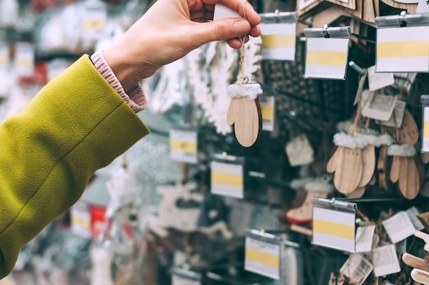 Девушка в магазине держит в руке варежки новогодние декоративные украшения.