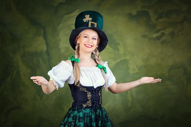 성 패트릭의 옷을 입은 소녀는 녹색 배경에 환영받습니다.