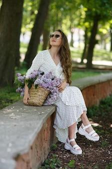 하얀 드레스와 선글라스를 쓴 소녀는 꽃이 든 고리버들 바구니를 손에 들고 있습니다. 라일락 바구니입니다. 소녀와 꽃입니다. 라일락 바구니를 손에 들고 앉습니다. 꽃집