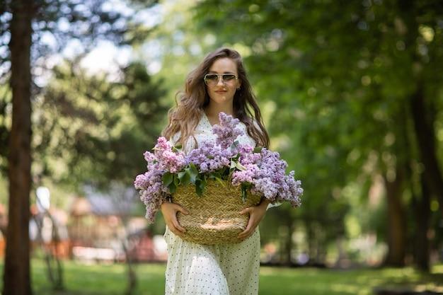 하얀 드레스와 선글라스를 입은 소녀는 꽃이 든 고리버들 바구니를 손에 들고 있습니다. 라일락 바구니입니다. 소녀와 꽃입니다. 라일락 바구니를 손에 들고 걷습니다. 꽃집. 봄 라일락 꽃입니다.