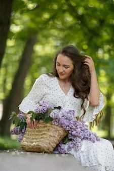 흰 드레스를 입은 소녀는 꽃이 든 고리버들 바구니를 손에 들고 있습니다. 라일락 바구니입니다. 소녀와 꽃입니다. 라일락 바구니를 손에 들고 앉습니다. 꽃집
