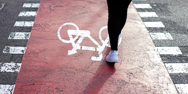 Девушка в белых кроссовках проходит по пешеходному переходу с велосипедной дорожкой. знак велосипеда покрашенный на асфальте.