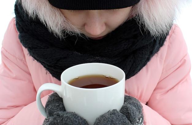 Девушка замерзла и держит чашку горячего чая, чтобы согреться. зимний морозный день. мужчина тепло одет в куртку, варежки и закутан в шарф.