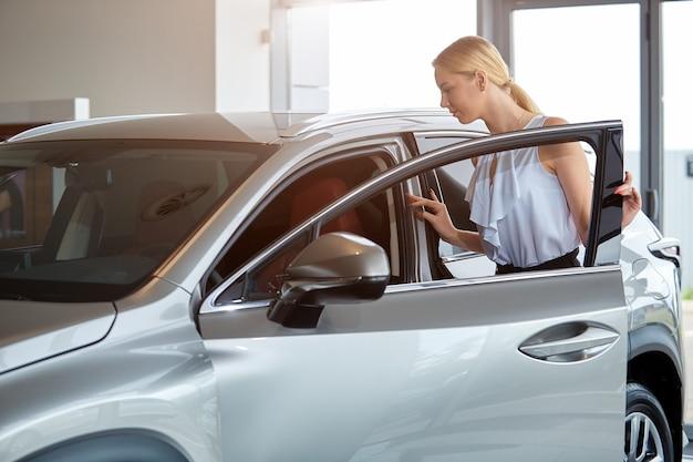 女の子はディーラーで新しい車を買うことを考えています