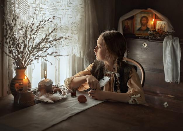 少女は卵を塗ることに気を取られ、窓の外を見ています。テーブルで若い女の子の肖像画。ロシアの村でイースターの準備をしています。