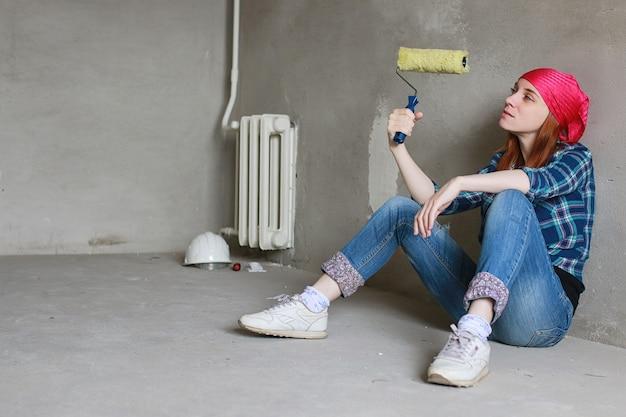 그 소녀는 아파트에서 수리를 하고 있습니다. 새 아파트로 이사하는 집. 작업자는 수리를 하고, 회반죽을 바르고, 벽을 뚫습니다.