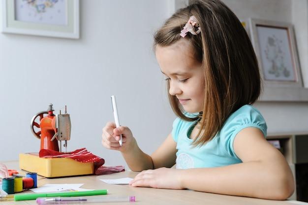 女の子は人形のドレスのスケッチを描いています。ミシンで縫うこと。