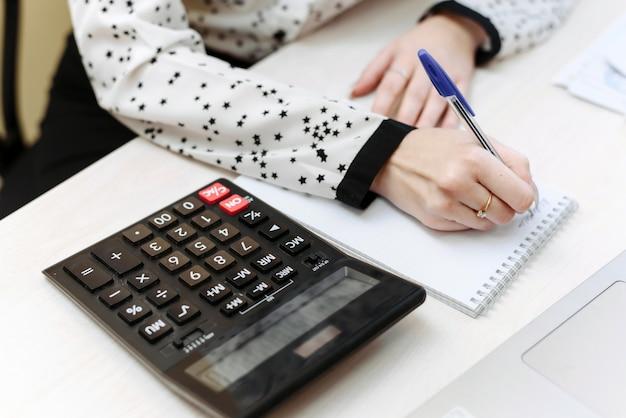 その少女は会計に従事している。女性の手は、家の支出と収入をノートに書き込みます。現金の分配、家計の遵守の概念