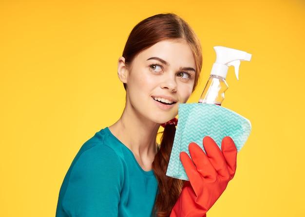Девушка занимается чисткой и дезинфекцией в резиновых перчатках.