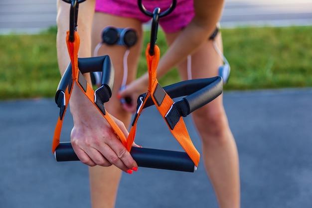 女の子は電気刺激装置でフィットネスに従事しています。電気刺激装置を使用して、運動と脚の筋肉への負荷をかけます。