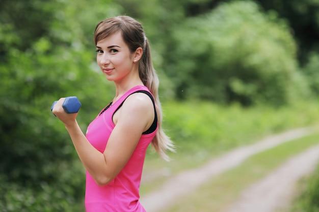 女の子は、自然の森でウェイトのあるスポーツに従事しています。健康な暮らし