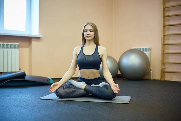 소녀는 훈련 후 체육관에서 스트레칭과 요가에 종사하고 있으며 격리 후 스포츠 클럽에서 수업 인 필라테스에 종사하고 있습니다.