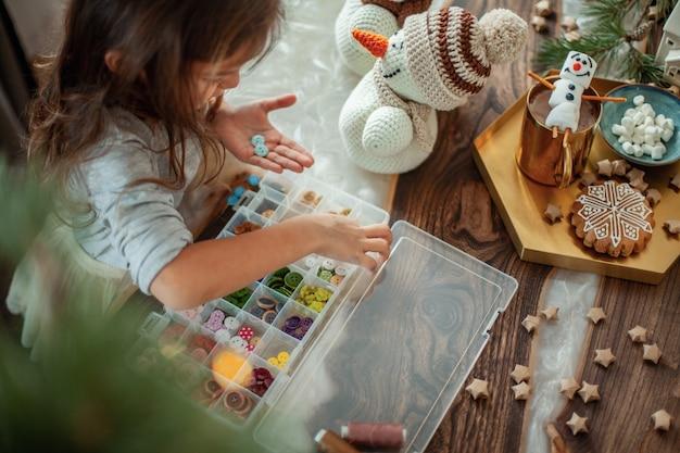 소녀는 크리스마스를 준비하고 있으며 버튼으로 니트 눈사람을 장식합니다. 새해 장식 개념. 진저 브레드 쿠키가 테이블에 있습니다. 코코아와 크리스마스 나무 가지.