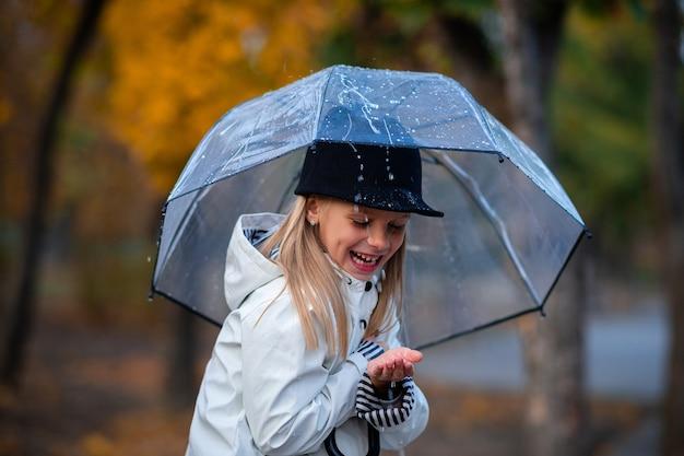 Девушка прячется от дождя под зонтиком. осенний парк