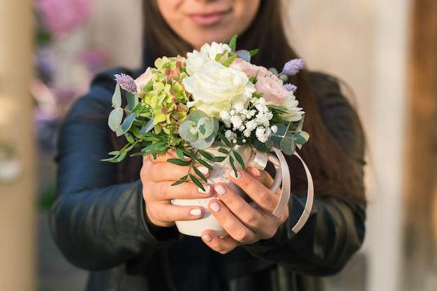 女の子は彼女の手に美しい花束を持っています