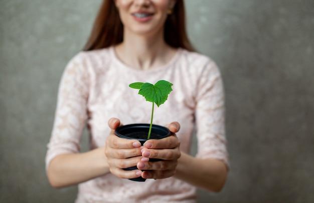 Девушка держит черный горшок с зеленым растением на темном фоне