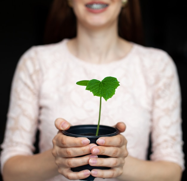 Девушка держит черный горшок с зеленым растением на темном фоне. рассада огурцов в горшке, готова к посадке в грунт. защита окружающей среды. уважение к природе