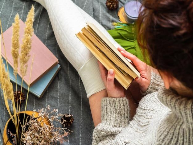 Девушка держит книгу. девушка в вязаном свитере в окружении множества книг.