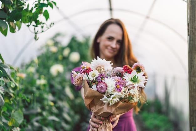 女の子は花束を手に持っています。花束に焦点が当てられています。フラワーアレンジメント。花と植物学。