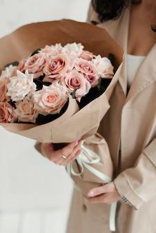 소녀는 꽃다발을 들고있다. 선물로 장미 꽃다발. 꽃의 인공 꽃다발. 종이 포장에 장식 꽃다발.