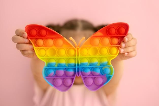 그 소녀는 나비 모양의 밝고 화려한 포핏 장난감을 들고 있다