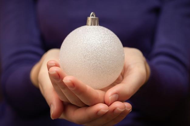 女の子はクリスマスツリーのおもちゃ、年末年始、クリスマスを持っています