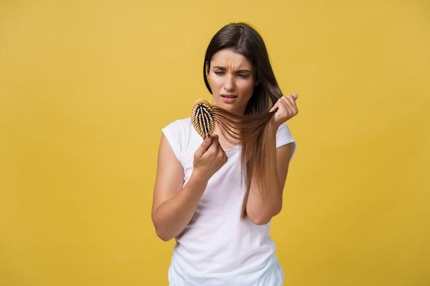 女の子は髪の毛が抜けた状態で櫛を持っています。髪の健康の概念。