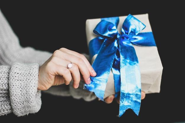 소녀는 그녀의 손에 파란 활과 함께 선물을 들고있다. 공예 종이 선물. 아름 다운 푸른 나비. 새해. 놀라다