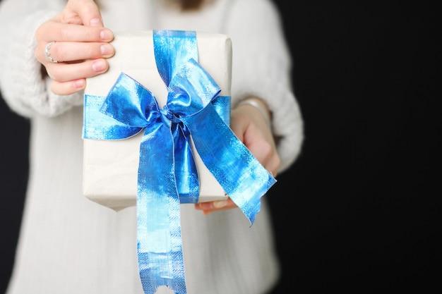 소녀는 그녀의 손에 파란 활과 함께 선물을 들고있다. 공예 종이 선물.