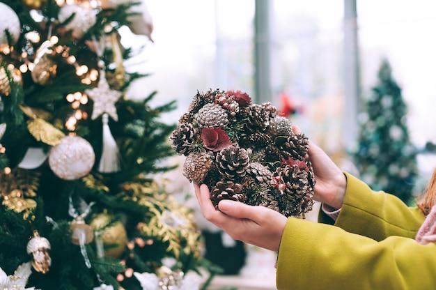소녀는 손에 새해 화환을 들고 있습니다. 상점에있는 크리스마스 트리의 배경.
