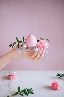 Девушка держит розовое пасхальное яйцо на подставке, розовый и мраморный фон, минимализм, цветы