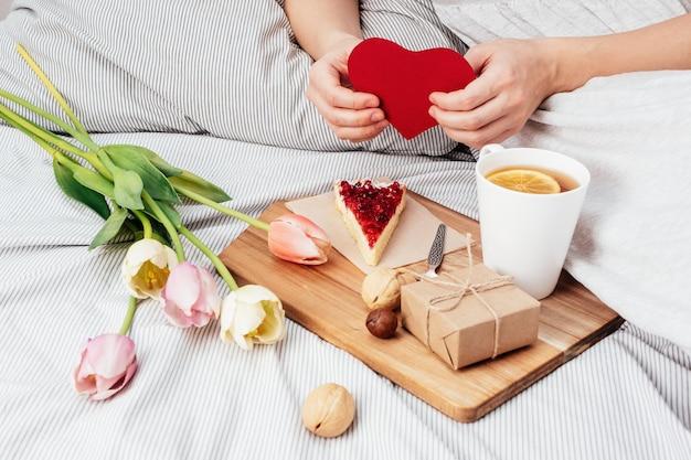 Девушка держит красное сердце. поздравление с днем всех влюбленных 14 февраля. завтрак в постель и подарок.