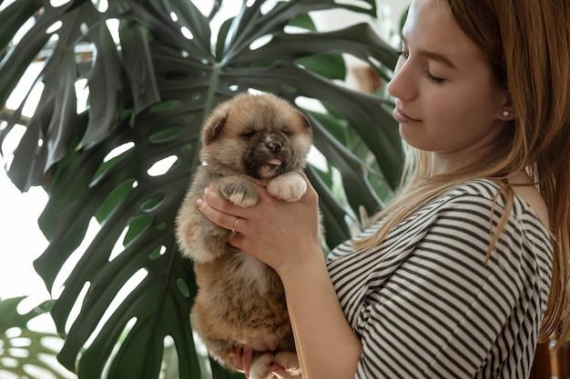 소녀는 그녀의 팔에 작은 솜털 신생아 강아지를 안고있다