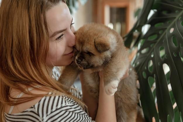 女の子は彼女の腕に小さなふわふわの新生児の子犬を持っています