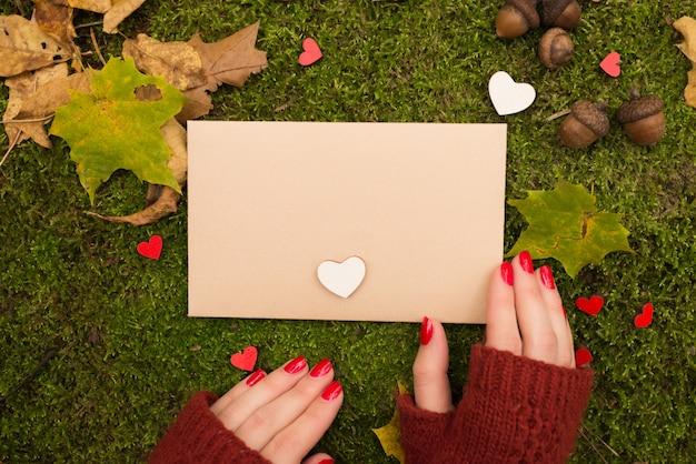 여자는 가을 공원에서 빈티지 빈 종이를 들고있다.
