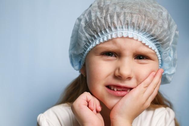 소녀는 손으로 뺨을 잡고 치아가 아파요.