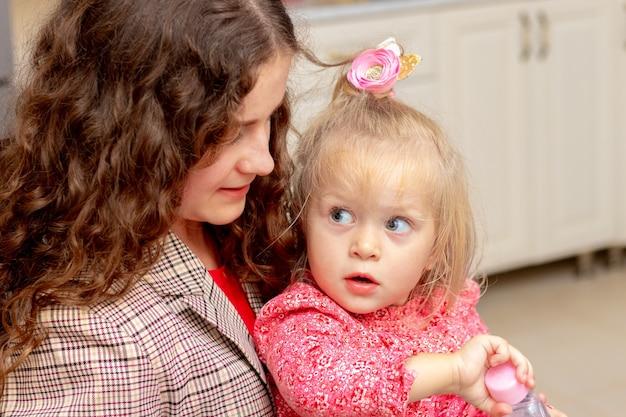 소녀는 그녀의 작은 조카를 잡고 있습니다. 성인 소녀와 어린 소녀