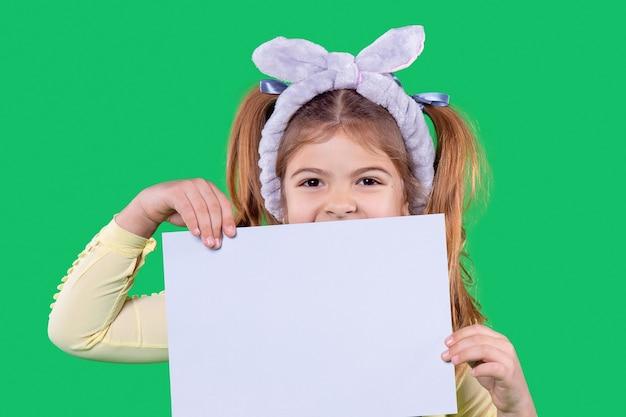 그 소녀는 입을 닫고 있는 손에 종이를 들고 있고 그녀의 머리에는 보라색 붕대 귀가 있습니다
