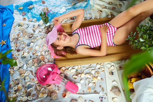 Девушка лежит на вымышленном пляже у моря или океана, загорает.