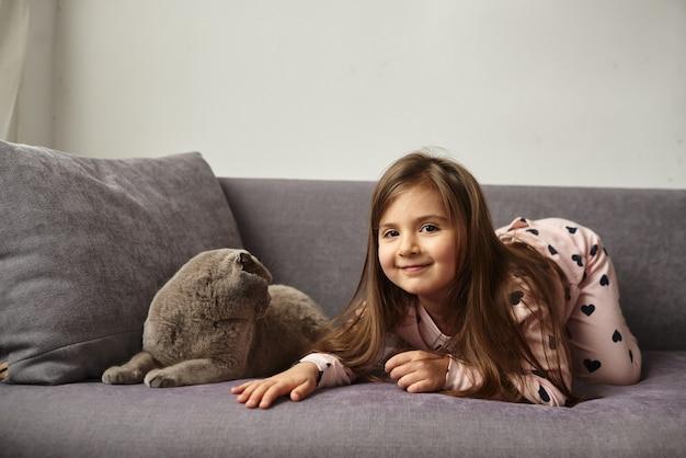 女の子はソファに横になって猫と遊んでいます