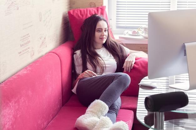 Девушка лежит на диване и улыбается, глядя в монитор.