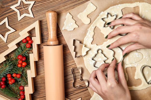 Девушка лепит имбирное рождественское печенье из формы для готовки