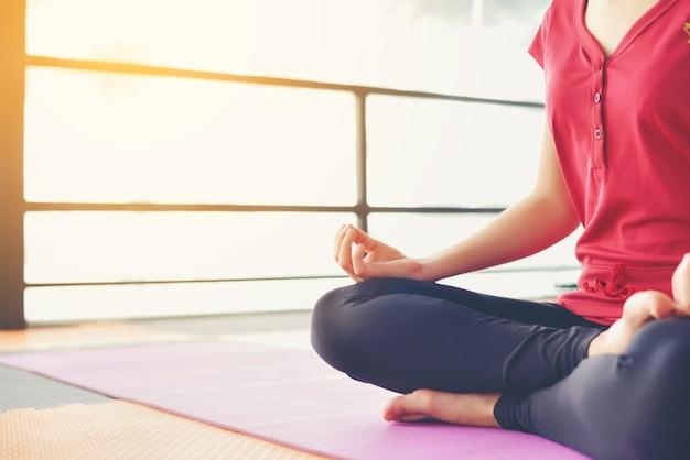女の子はピンクのゴムの床に健康を瞑想しています。この画像は柔らかいです。