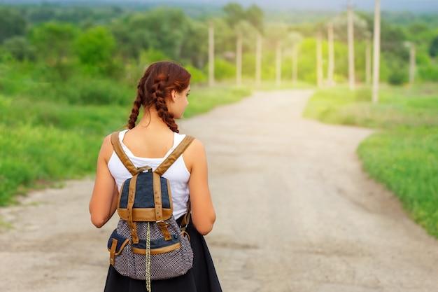 女の子はバックパックで道を進んでいます