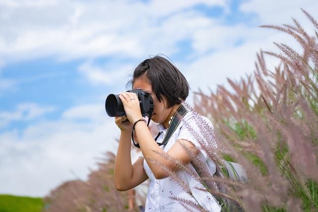 女の子は美しい牧草地を旅しながらプロの写真を練習しています。