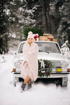 Девушка готовится к рождеству, накрывается одеялом на фоне ретро-автомобиля, на крыше которого стоят елки, подарки и венок в зимнем снежном лесу.