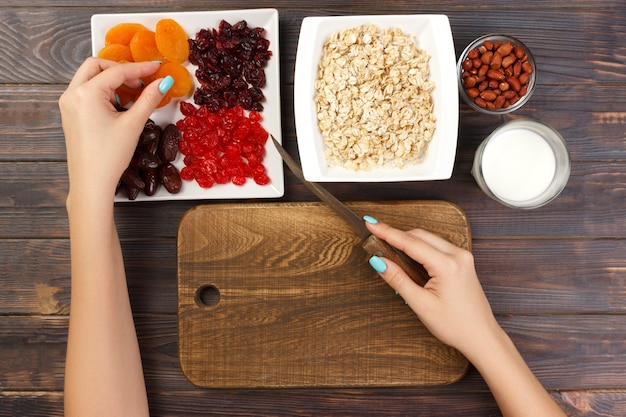 Девушка готовит завтрак. нарезать сухофрукты на овсяную кашу на разделочной доске. полезный и полезный завтрак. темный деревянный фон, вид сверху.